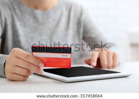 Concept for Internet shopping: hands with digital tablet and credit card