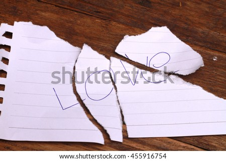 Concept for lost of love or broken love , torn paper on wood table. - stock photo