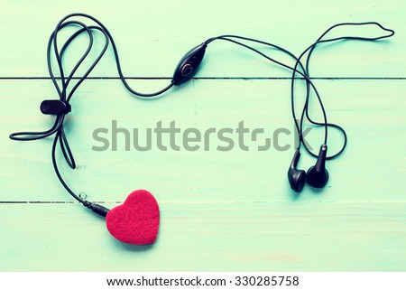 Concept for love music. Earphones connected to the heart. Image toned with retro filter. - stock photo