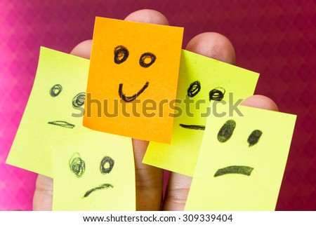 concept for optimism with paper faces on multiple fingers one with a happy good attitude - stock photo