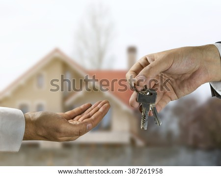 Concept for purchasing a new house. Real estate agent giving house keys to the new owner in front of the house.
