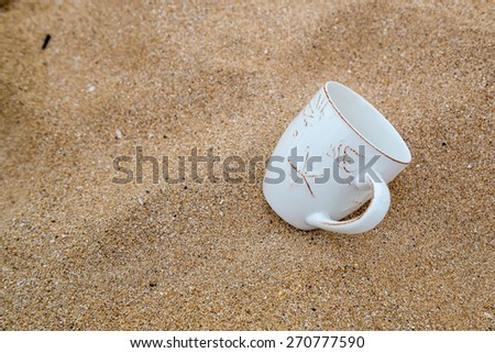 Concept for relaxation, coffee mug in sand - stock photo
