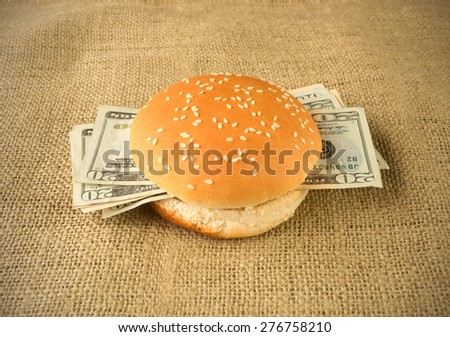Concept for rich and greedy - Burger buns stuffed with money - stock photo