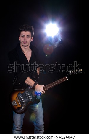Concept for rock concert. Artistic image of young cool man  playing electric guitar. Image taken in studio with back light and lens flare. - stock photo