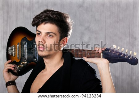 Concept for rock concert. Artistic image of young cool man  with electric guitar. Image taken in studio with backlight and lens flare.