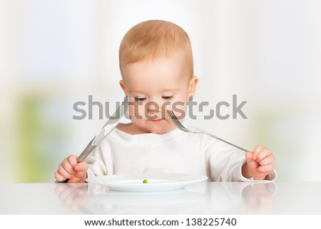 concept. funny baby with fork and knife eating, looking at the plate with one pea