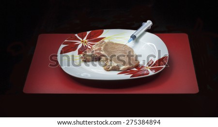 Concept genetically modified organism: syringe and raw meat on a dish isolated on a black background - stock photo