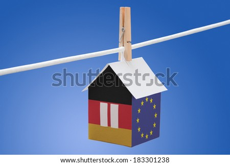 concept - Germany and EU flag painted on a paper house hanging on a rope - stock photo