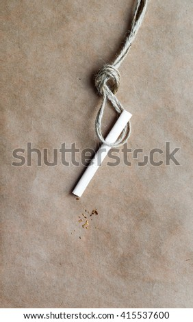 concept hangman's knot on kraft paper background with cigarette - stock photo