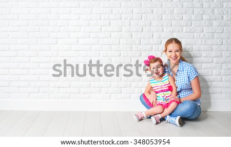 concept happy family mother and baby daughter, a girl at a blank brick wall of a house move - stock photo