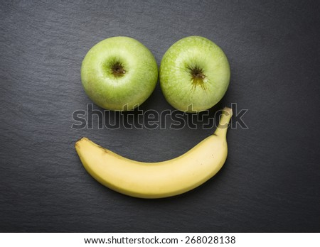 """Concept """"healthy is good"""": Smiley face with fresh apples and banana looking happy and smiling, isolated on dark grey stone plate. - stock photo"""