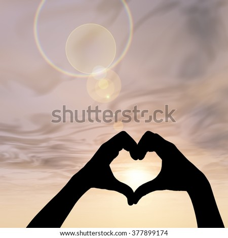 Concept heart shape or symbol made of human or woman and man hand silhouette over a sky at sunset background metaphor to love, valentine, romantic, couple, wedding, romance, summer or sunrise