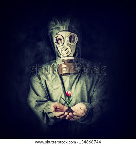 Concept. Hope after environmental protection. Man in gas mask holding tulip flower in palms - stock photo