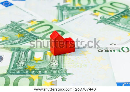Concept house sell, foreclosure, debt, bill, mortgage on hundred euro banknotes. Focus on red house. - stock photo