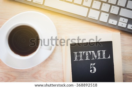 Concept HTML5 message on wood boards. A keyboard and a glass coffee table.Vintage tone. - stock photo