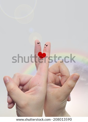 Concept human or female hands with two fingers painted with a red heart and smile faces over rainbow sky background, metaphor to love, valentine, romantic, couple, wedding, romance, summer or sunrise - stock photo