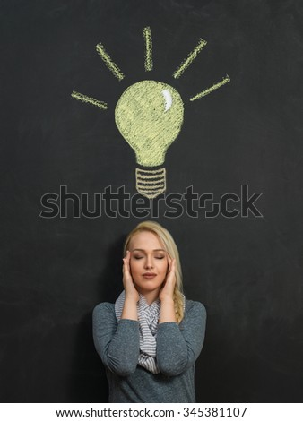 concept idea. a woman and a light bulb drawn in chalk on a blackboard