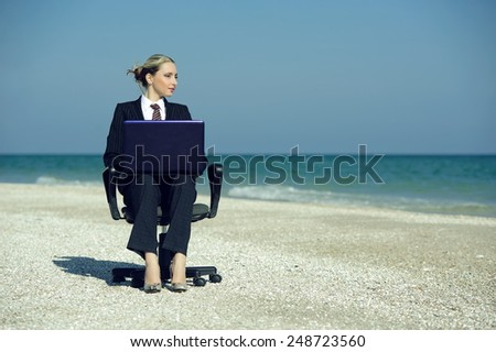 Concept illustrating remote work, business woman with laptop and office chair on the beach