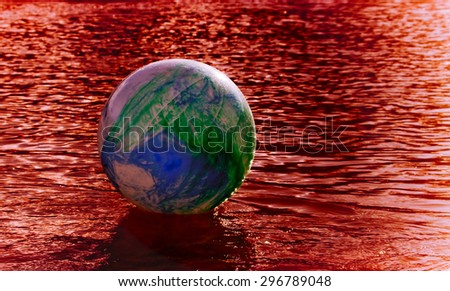 concept image for global environmental issue using inflatable rubber ball with earth like markings and blood colored  rippled water surface  - stock photo