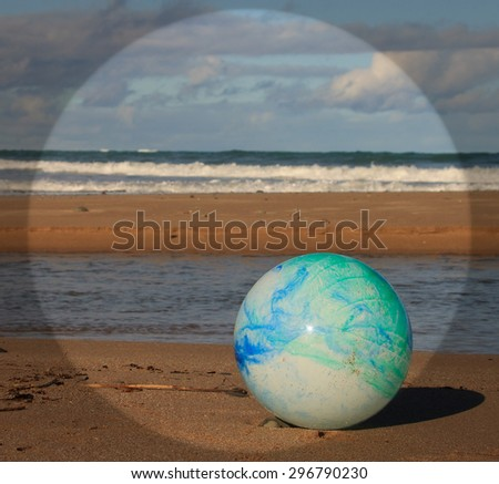 concept image for global environmental issue using inflatable rubber ball with earth like markings and rippled water surface