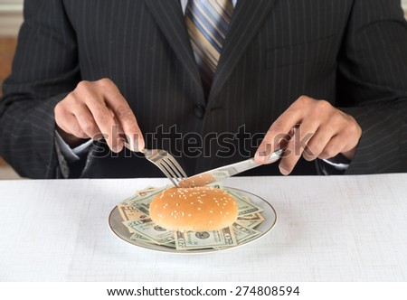 Concept image for greedy corporate executives and financial fraud. Executive is eating a burger on a plate stuffed with dollar bills. He is wearing a black suit and blue tie.  - stock photo