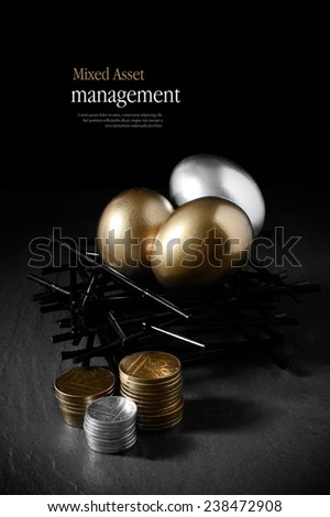 Concept image for mixed asset financial management. Mixed gold and silver goose eggs in a stark birds nest and stacked coins against a black background. Copy space. - stock photo