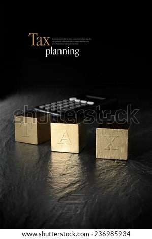 Concept image for tax management and tax return. Creatively lit calculator and gold blocks against a black background. Copy space. - stock photo