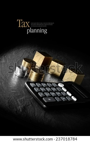 Concept image for tax management and tax return. Creatively lit calculator and gold blocks and coins against a black background. Copy space. - stock photo