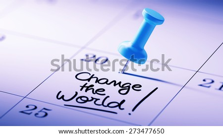 Concept image of a Calendar with a blue push pin. Closeup shot of a thumbtack attached. The words Change the world written on a white notebook to remind you an important appointment. - stock photo