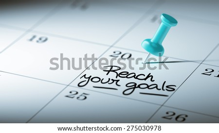 Concept image of a Calendar with a blue push pin. Closeup shot of a thumbtack attached. The words Reach your goals written on a white notebook to remind you an important appointment. - stock photo