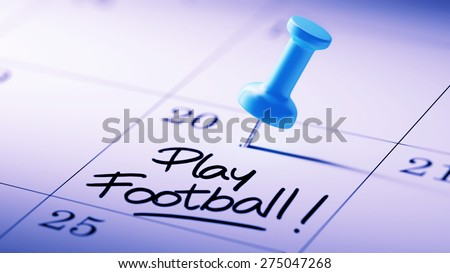 Concept image of a Calendar with a blue push pin. Closeup shot of a thumbtack attached. The words Play Football written on a white notebook to remind you an important appointment. - stock photo
