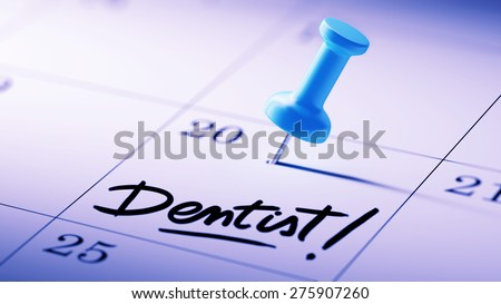 Concept image of a Calendar with a blue push pin. Closeup shot of a thumbtack attached. The words Dentist! written on a white notebook to remind you an important appointment. - stock photo