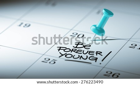 Concept image of a Calendar with a blue push pin. Closeup shot of a thumbtack attached. The words Be Forever young written on a white notebook to remind you an important appointment. - stock photo