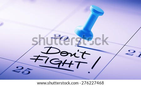 Concept image of a Calendar with a blue push pin. Closeup shot of a thumbtack attached. The words Don't Fight written on a white notebook to remind you an important appointment. - stock photo