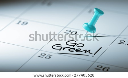 Concept image of a Calendar with a blue push pin. Closeup shot of a thumbtack attached. The words Go Green written on a white notebook to remind you an important appointment. - stock photo