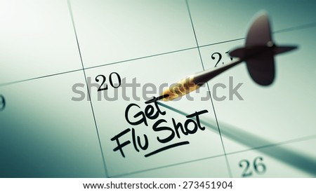 Concept image of a Calendar with a golden dart stick. The words Get Flu Shot written on a white notebook to remind you an important appointment.