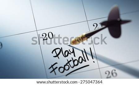 Concept image of a Calendar with a golden dart stick. The words Play Football written on a white notebook to remind you an important appointment. - stock photo
