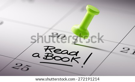 Concept image of a Calendar with a green push pin. Closeup shot of a thumbtack attached. The words Read a book written on a white notebook to remind you an important appointment. - stock photo