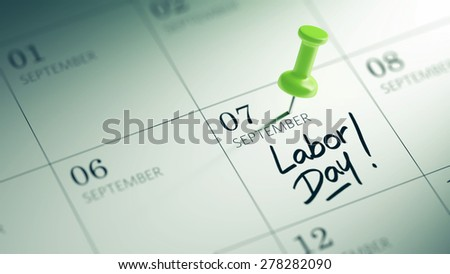 Concept image of a Calendar with a green push pin. Closeup shot of a thumbtack attached. The words Labor Day written on a white notebook to remind you an important appointment. - stock photo
