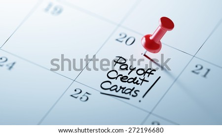 Concept image of a Calendar with a red push pin. Closeup shot of a thumbtack attached. The words Pay off Credit cards written on a white notebook to remind you an important appointment. - stock photo