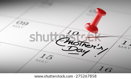 Concept image of a Calendar with a red push pin. Closeup shot of a thumbtack attached. The words Mother's Day written on a white notebook to remind you an important appointment. - stock photo