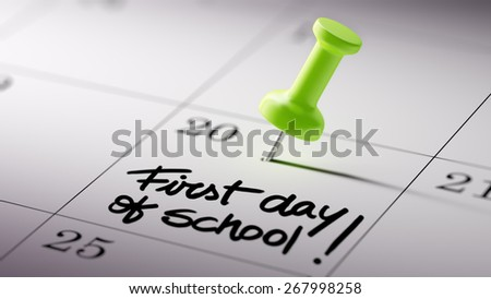 Concept image of a Calendar with a shiny green push pin. Closeup shot of a thumbtack attached. First day of school text note reminder concept. Words First day of school written in Black Marker. - stock photo