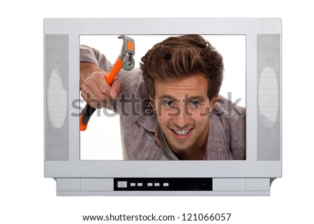 Concept image of a man hammering inside a television