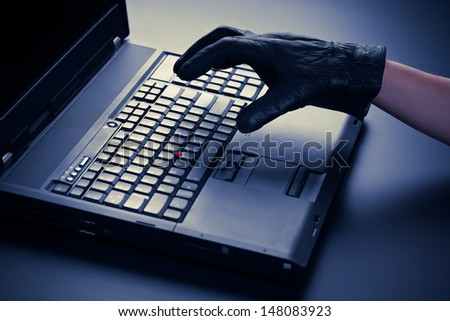 Concept image of a thief's hand over a business class mobile computer - security breach.