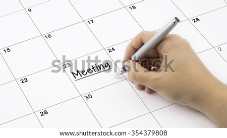 Concept image of calendar with a woman hand writing. Words Meeting written on calendar to remind you an important appointment. - stock photo