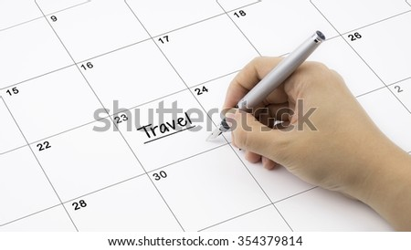 Concept image of calendar with a woman hand writing. Words Travel written on calendar to remind you an important appointment. - stock photo
