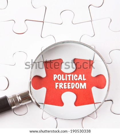 Concept image of missing jigsaw puzzle pieces found by magnifying glass revealing the POLITICAL FREEDOM words. - stock photo