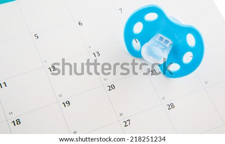 Concept image of pregnancy delivery due date with calendar page and blue pacifier. - stock photo