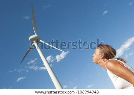 Concept image of woman blowing and generating a modern high rising wind mill tower and its blades as a symbol for renewable energy, isolated with blue sky as background and copy space. - stock photo
