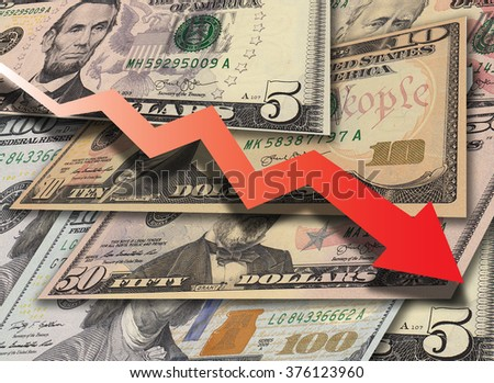 Concept image with pile of dollar banknotes in different currency 5, 10, 50, 100 dollar currency of the United States useful as a background with big red arrow graph pointing down - stock photo